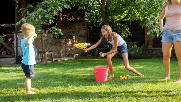 Imagem de família feliz e alegre brincando no jardim do quintal. pessoas espirrando água com pistolas de água e mangueira de jardim.
