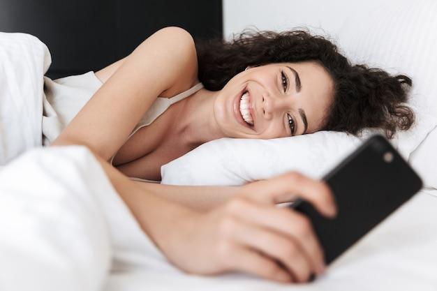 Imagem de feliz mulher caucasiana de 20 anos com cabelo escuro e encaracolado, deitada na cama sobre uma almofada branca em um quarto de hotel e olhando para o celular com um sorriso