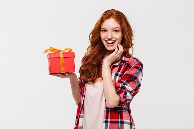 Imagem de feliz mulher ruiva de camisa segurando a caixa de presente