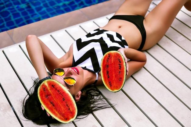 Imagem de férias de estilo de vida de moda de mulher sexy elegante, posando perto da piscina em suas férias, usando biquíni de estilo geométrico e óculos escuros, deitado perto da piscina, segurando uma grande e saborosa melancia doce.