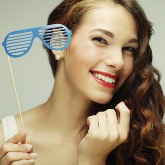 Imagem de festa. mulheres jovens brincalhões segurando um óculos de festa.