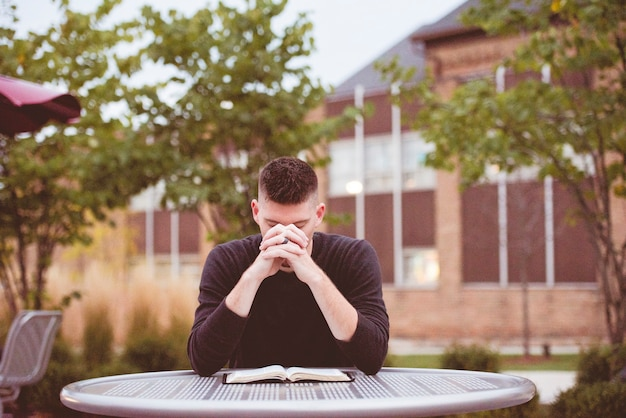 Imagem de foco raso de um homem orando com uma bíblia aberta