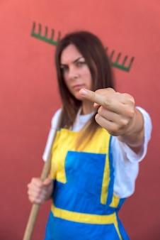 Imagem de foco raso de uma jovem mulher mostrando o dedo médio