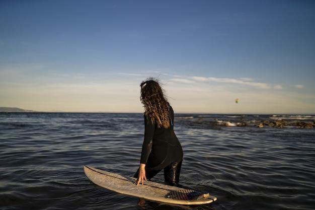 Imagem de foco raso de uma mulher caminhando no mar com uma prancha de surfe ao lado