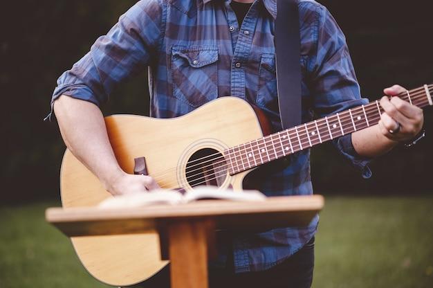 Imagem de foco superficial de um homem tocando violão perto de um suporte para discurso