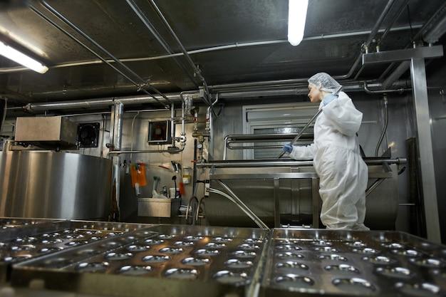 Imagem de fundo de ângulo baixo da esteira transportadora industrial na fábrica de produção de alimentos limpos com uma trabalhadora irreconhecível, copie o espaço