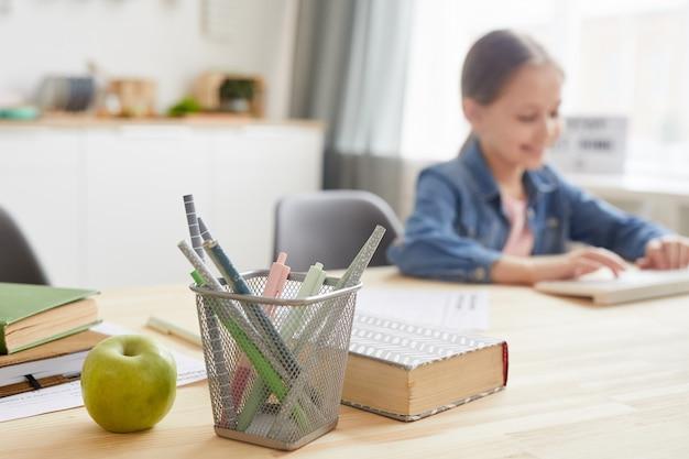 Imagem de fundo de menina usando laptop enquanto estudava em casa, foco no suporte de lápis e livros, espaço de cópia