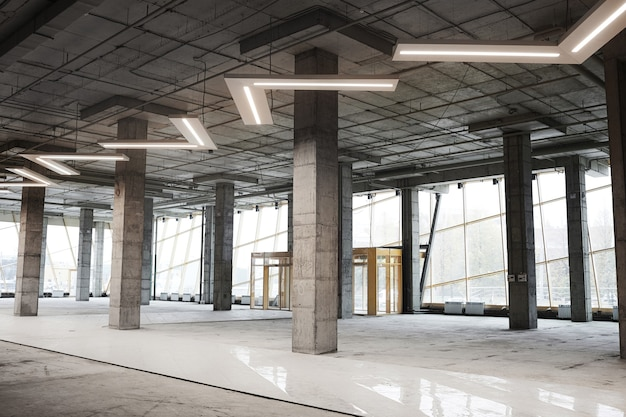 Imagem de fundo de um prédio vazio em construção com colunas de concreto e lâmpadas gráficas de teto,