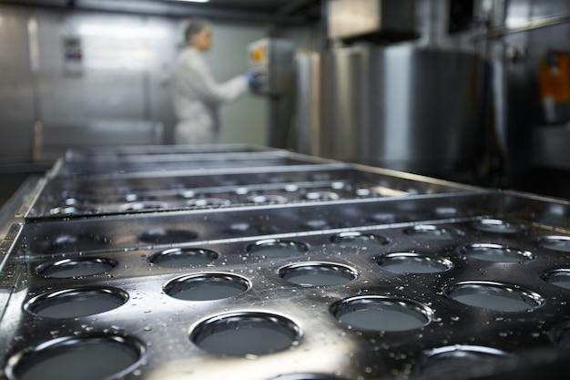 Imagem de fundo de uma esteira transportadora industrial em uma fábrica de produção de alimentos limpos com uma trabalhadora irreconhecível, copie o espaço