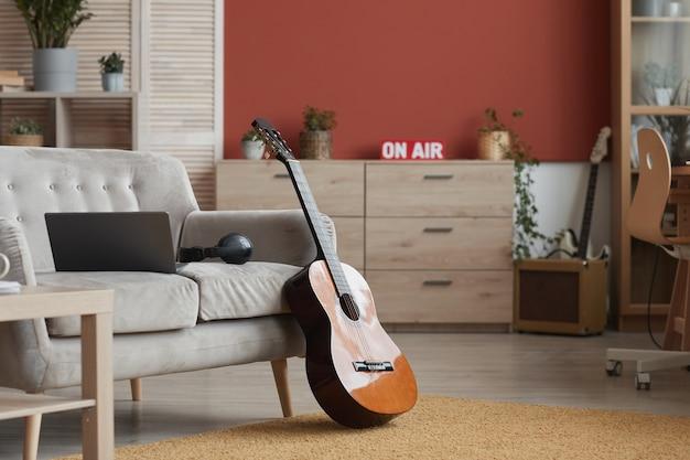 Imagem de fundo do interior de uma sala moderna com instrumentos musicais e sinal no ar, foco na guitarra em primeiro plano, copie o espaço