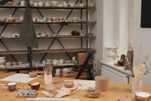 Imagem de fundo em tons quentes da oficina de cerâmica vazia com mesa de madeira e ferramentas em primeiro plano, copie o espaço