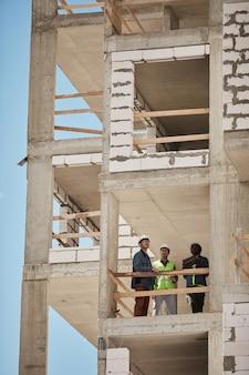 Imagem de fundo vertical de um canteiro de obras alto com um grupo de trabalhadores copie o espaço