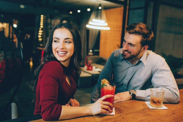 Imagem de garota feliz sentado com um cara bonito no bar. ela está olhando para algum lugar de lado e sorrindo. jovem está olhando para ela e sorrindo também.