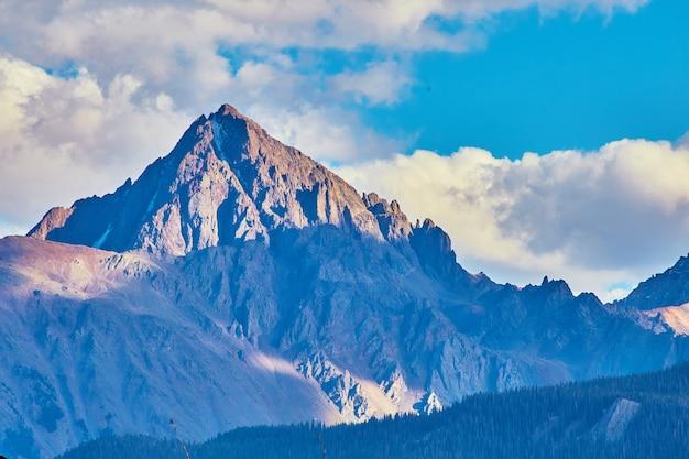 Imagem de grande montanha rochosa com neve e raios de sol