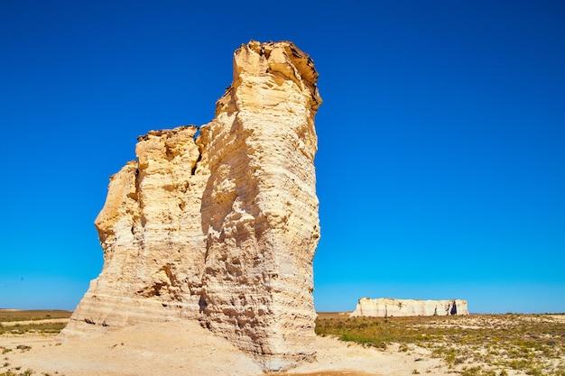 Imagem de grandes pilares de rocha branca saindo de um deserto plano e um céu azul intenso