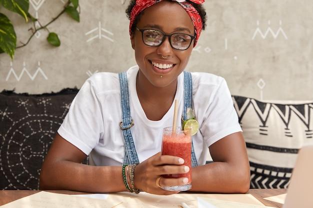 Imagem de hipster alegre usando óculos transparentes, vestido com roupa casual, bebendo coquetel fresco