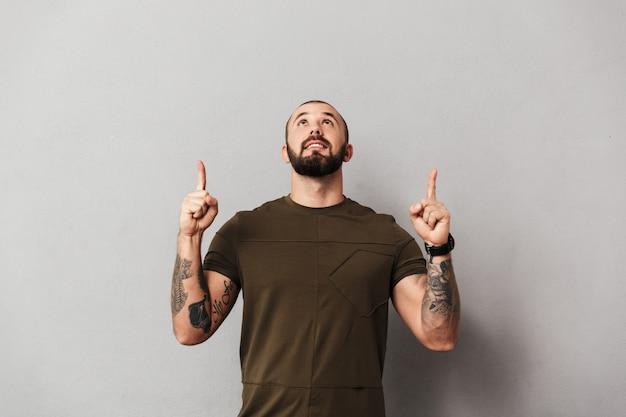 Imagem de homem barbudo com tatuagens nos braços, olhando para cima com os dedos apontando na copyspace, isolado sobre a parede cinza