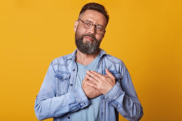 Imagem de homem barbudo satisfeito com óculos ópticos arredondados, mantém as mãos no peito, veste jaqueta jeans elegante