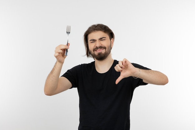 Imagem de homem barbudo segurando o garfo e mostrando o polegar para baixo.