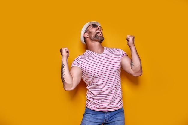 Imagem de homem barbudo tatuado animado em óculos escuros e chapéu fazendo gesto de vencedor isolado amarelo ba ...