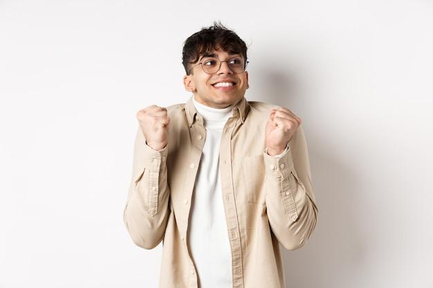Imagem de homem bonito e animado, sentindo-se motivado e com sorte, olhando certo e sorrindo, fazendo o gesto de levantar o punho para comemorar a vitória, ganhando o prêmio, em pé na parede branca.
