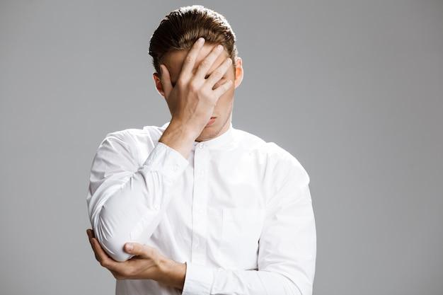 Imagem de homem caucasiano confuso, escondendo o rosto dele