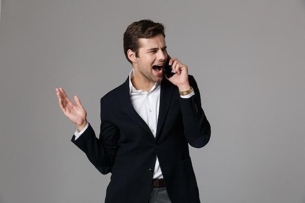 Imagem de homem caucasiano de 30 anos em um terno de negócio falando no celular preto, isolado sobre uma parede cinza