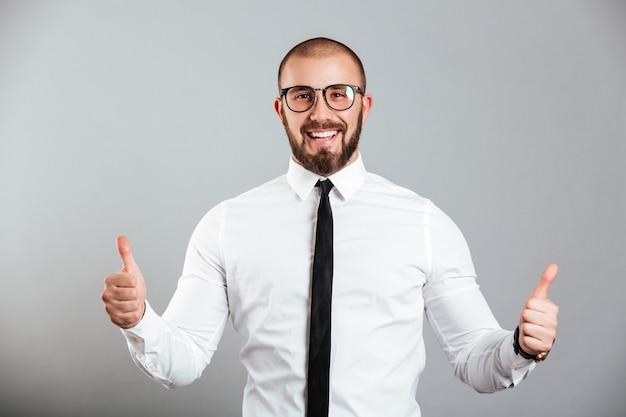 Imagem de homem caucasiano em êxtase na camisa branca e óculos sorrindo e mostrando os polegares, isolado sobre a parede cinza
