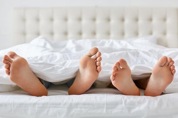 Imagem de homem e mulher com os pés descalços sob o cobertor no quarto.