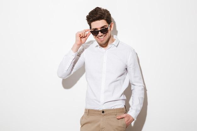 Imagem de homem feliz, vestido de camisa, olhando para a câmera debaixo de óculos de sol pretos e sorrindo mostrando dentes perfeitos, sobre espaço em branco com sombra