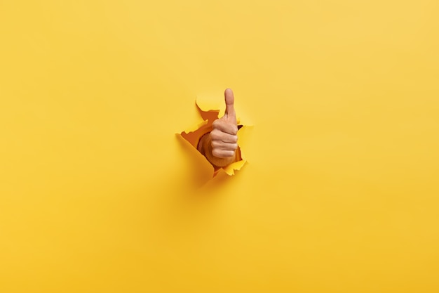 Imagem de homem irreconhecível fazendo gesto de polegar para cima