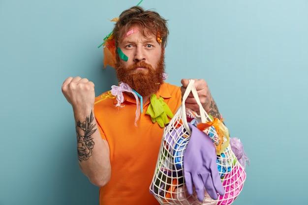 Imagem de homem ruivo irritado com barba espessa, mostra punho, demonstra gesto de advertência, segura coisas de plástico reciclável, fica encostado na parede azul. pessoas, meio ambiente, poluição