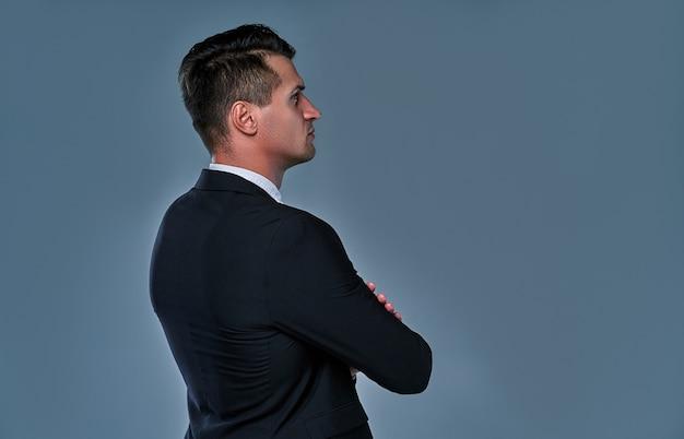 Imagem de homem sério bonito vestindo terno preto e branco, em pé sobre um fundo cinza, olhando de lado.