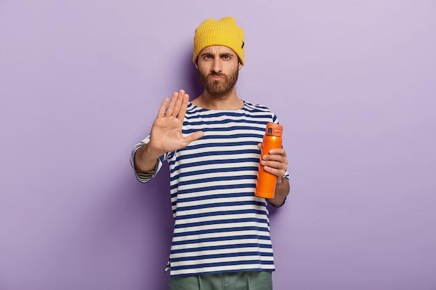 Imagem de homem sério e insatisfeito mostra sinal de recusa, faz gesto de pare com a palma da mão segura garrafa térmica bebe chá dentro de casa, não tem vontade de tomar café da manhã. pessoas