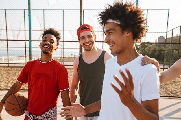 Imagem de homens caucasianos e americanos jogando basquete no parquinho ao ar livre, durante um dia ensolarado de verão