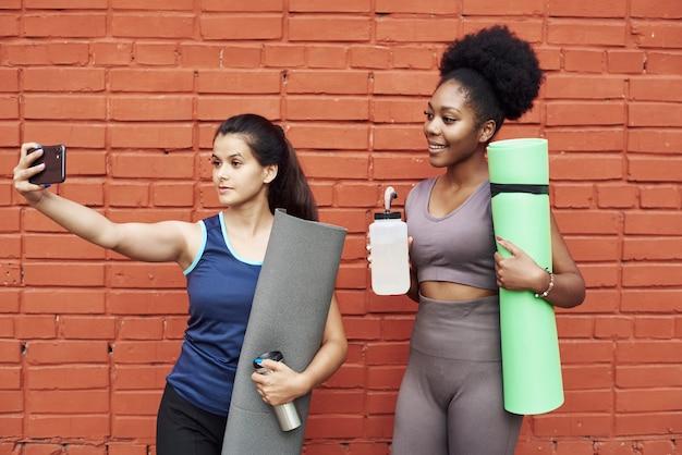 Imagem de incríveis jovens mulheres atléticas tomando uma selfie contra uma parede de tijolos.