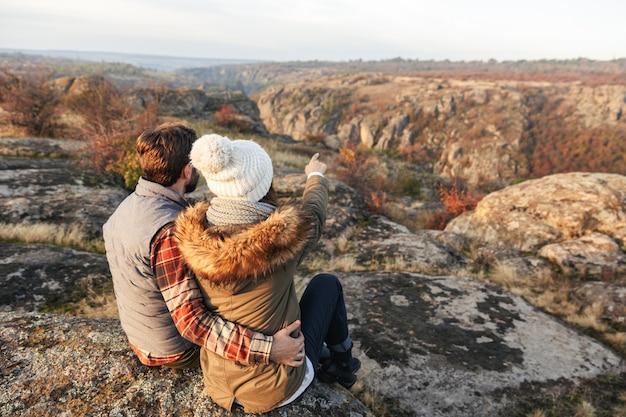 Imagem de incrível jovem casal apaixonado fora em férias alternativas gratuitas acampando sobre montanhas apontando.