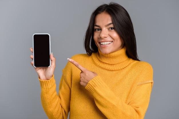 Imagem de incrível mulher animada posando isolada sobre uma parede cinza, mostrando o visor do telefone móvel.