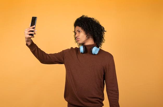 Imagem de jovem americano africano posando isolado sobre fundo amarelo, tirando uma selfie com o telefone.