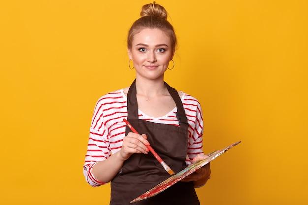 Imagem de jovem atraente agradável vestindo camiseta despojada, avental marrom e brincos, segurando o equipamento de tinta