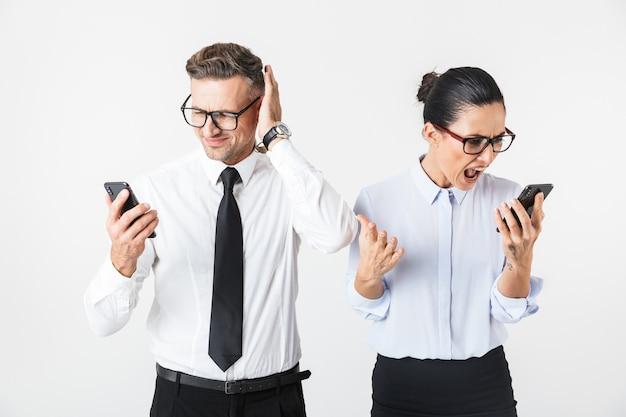 Imagem de jovem bravo gritando casal de colegas de trabalho isolado sobre uma parede branca, falando por telefones celulares.