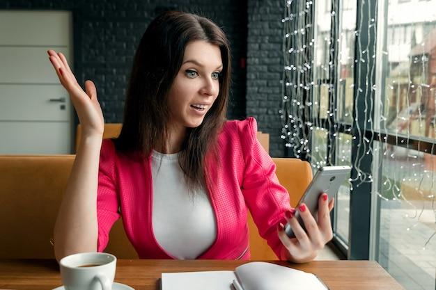 Imagem de jovem chocado animado mulher de negócios sentado dentro de casa usando telefone celular