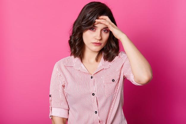 Imagem de jovem com dor de cabeça terrível, mantém a mão na testa, precisa tomar remédio, foto de estúdio de menina morena de blusa listrada, isolada sobre rosado