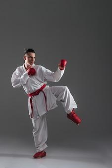 Imagem de jovem desportista na prática de quimono no karatê isolado sobre fundo cinza. olhe para o lado.