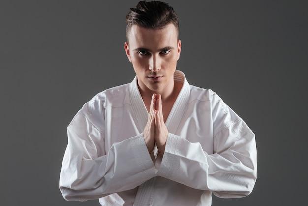 Imagem de jovem desportista vestido de quimono, gesticulando com as mãos sobre o fundo cinza. olhando para a câmera.