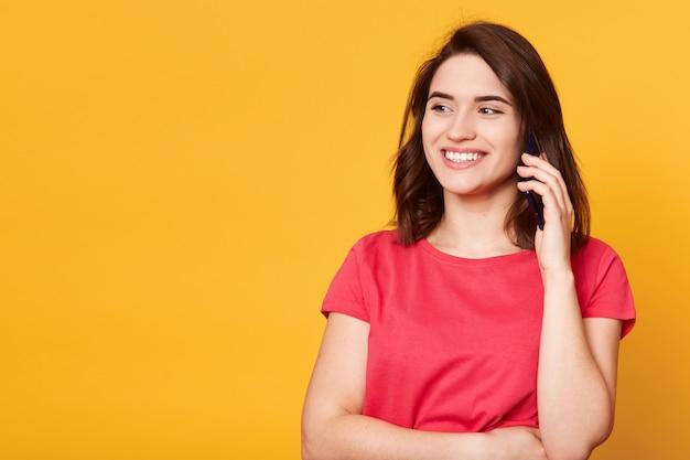 Imagem de jovem em camiseta vermelha casual, falando no celular, conduzindo a conversa