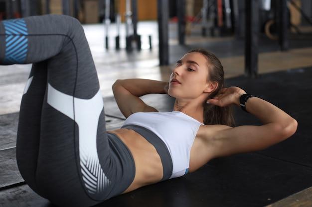 Imagem de jovem em roupas esportivas, fazendo abdominais no ginásio.