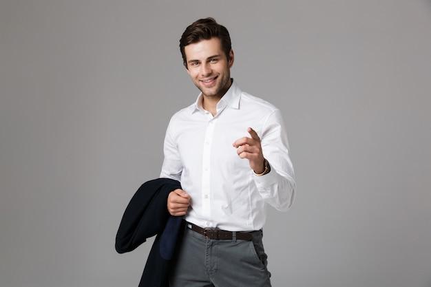 Imagem de jovem empresário dos anos 30 segurando uma jaqueta e apontando o dedo, isolada sobre uma parede cinza