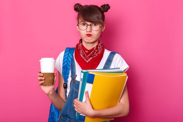 Imagem de jovem estudante segurando a prancheta e a xícara de café enquanto pensava em seu relatório, sente decepção, não gosta do tópico de seu ensaio, de mau humor, vestindo roupas da moda.