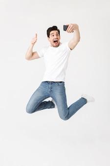 Imagem de jovem feliz animado posando isolado sobre uma parede branca usando telefone celular, tire uma selfie e faça um gesto de polegar para cima.